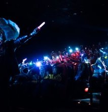 The crowd gets out glow sticks and smartphones during the performance of